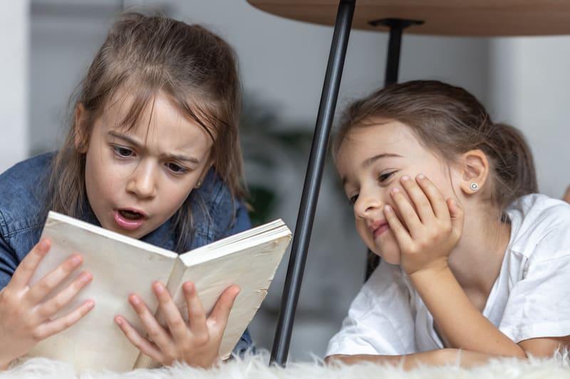Две маленькие сестры весело читают книгу, лежа на полу в своей комнате