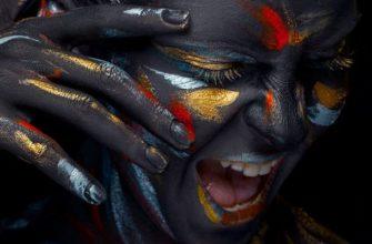 Лицо молодой женщины, которая покрыта черной краской