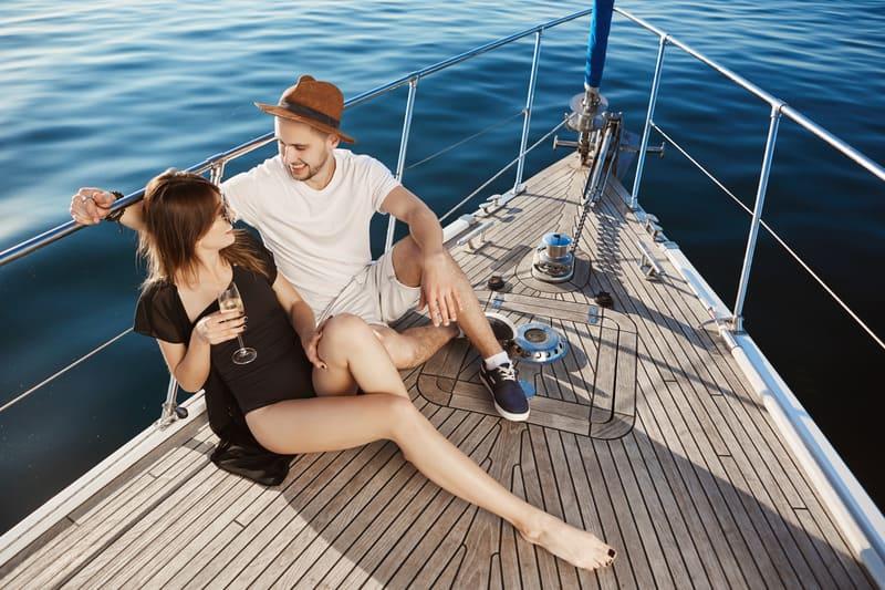 Молодая привлекательная пара сидит на смычке яхты
