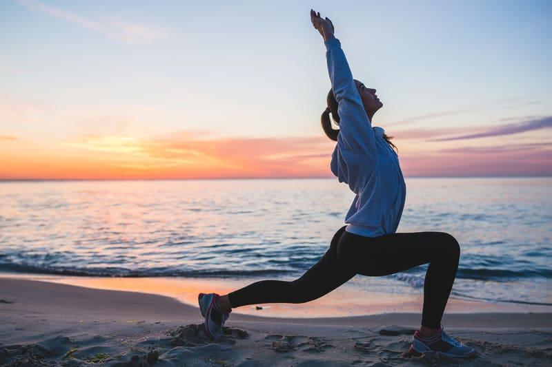 Молодая женщина делает спортивные упражнения на пляже
