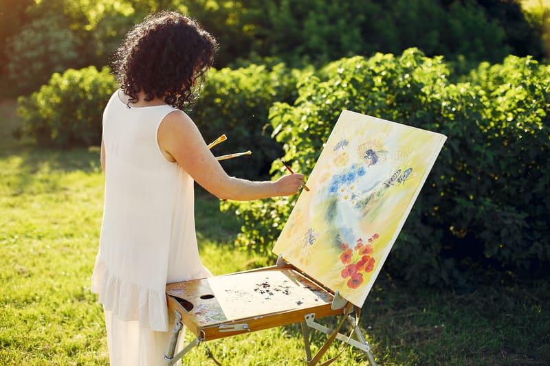 Взрослая женщина рисует на природе