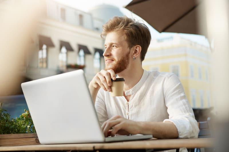 Взрослый рыжий мужчина сидит с ноутбуком на террасе ресторана