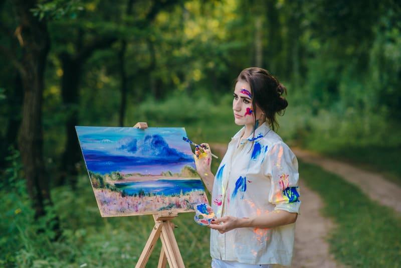 Женщина художница стоит около холста с кисточкой