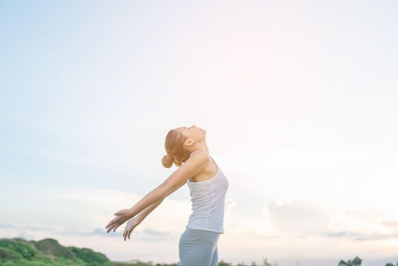 Женщина растянула руки на фоне неба