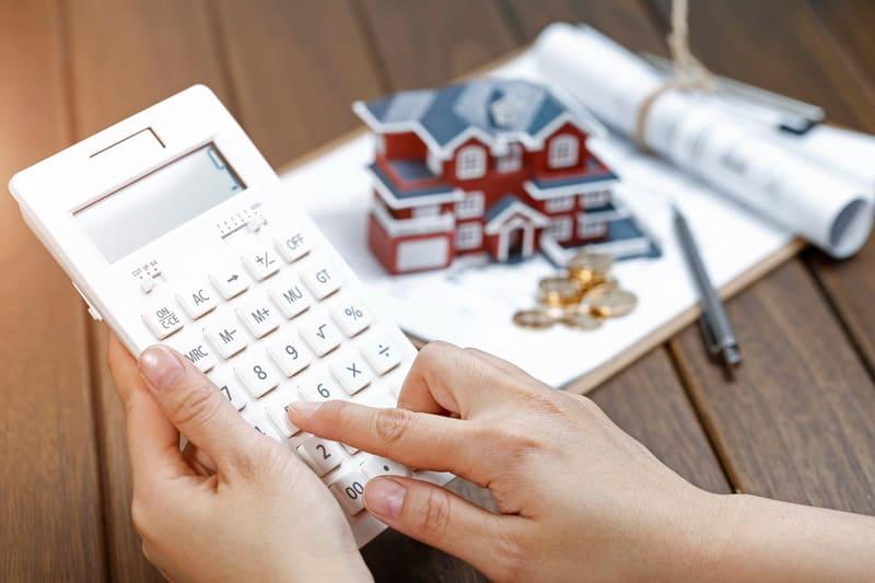 Женская рука, управляющая калькулятором перед моделью виллы